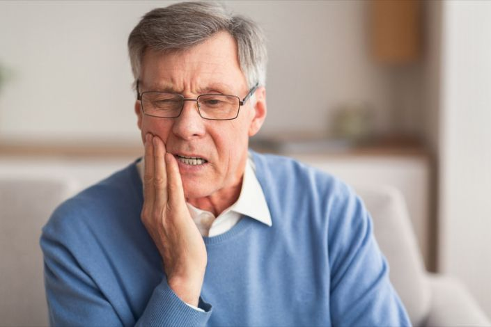 Older man suffering from tooth pain
